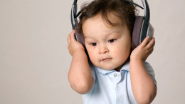 Baby with headphone,listens to music.